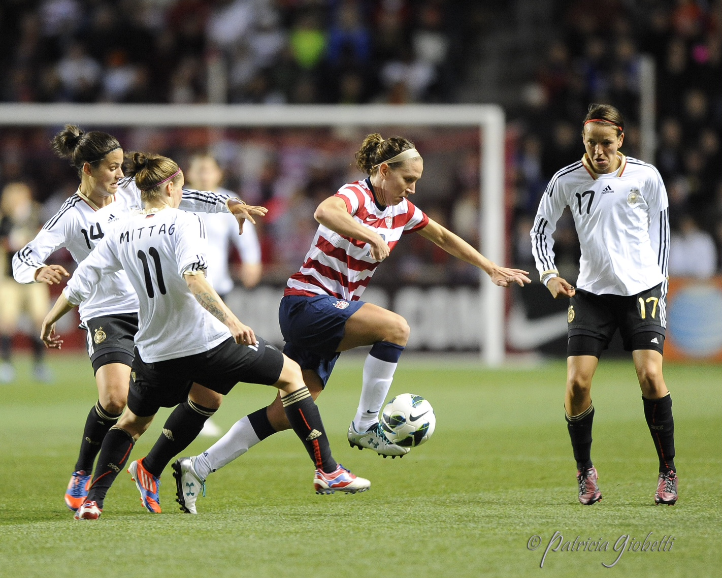 Lauren Cheney (center, with ball) dribbles avoids tackles from Germany players. (Copyright Patricia Giobetti | http://www.printroom.com/pro/psgiobetti)