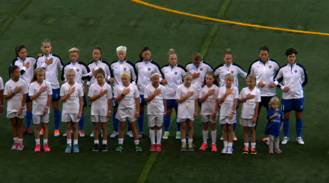 Megan Rapinoe did not kneel for the national anthem on Sunday, instead standing and locking arms with Seattle teammates.