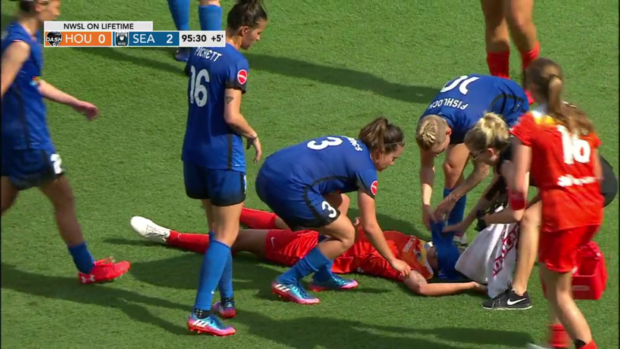 Rachel Daly is surrounded by Reign players after collapsing from heat exhaustion.