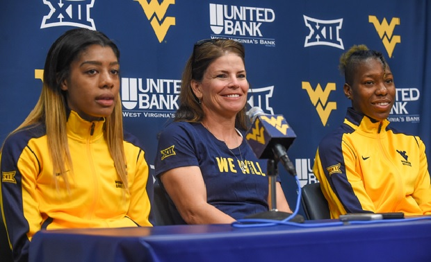 Ashley Lawrence (left) and Kadeisha Buchanan (right) sit with WVU head coach Nikki Izzo-Brown during a press conference earlier this season. (photo courtesy WVU Athletics)