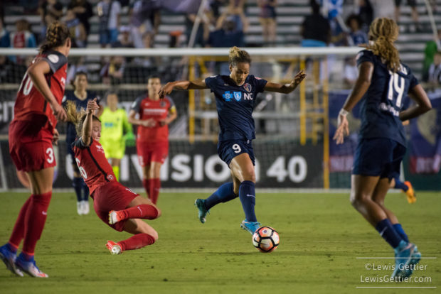 Lynn Williams tried to evade Emily Sonnett (sliding) during the first ever North Carolina Courage home match (photo copyright Lewis Gettier)