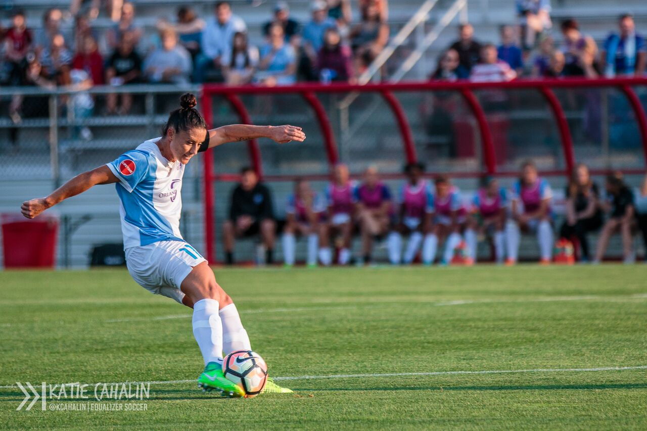 With her teammates looking on from the sidelines, Ali Krieger plays the ball in for the Pride. (photo copyright Katie Cahalin for The Equalizer)